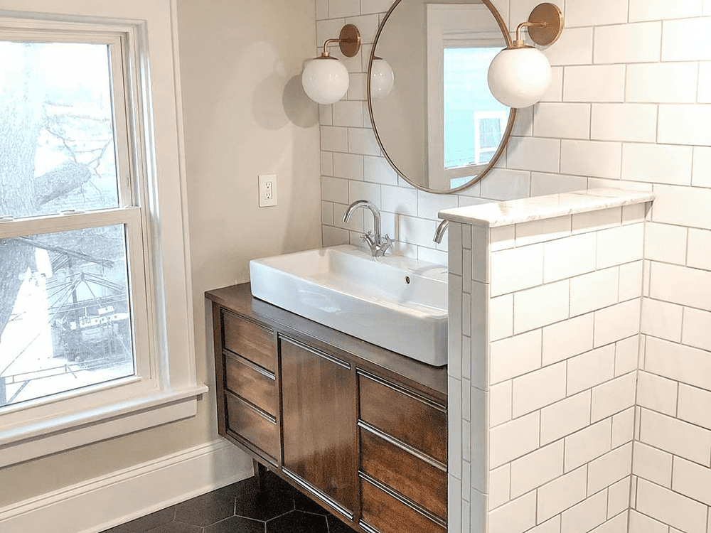 bathroom with big white tile circle mirror and two sphere lights