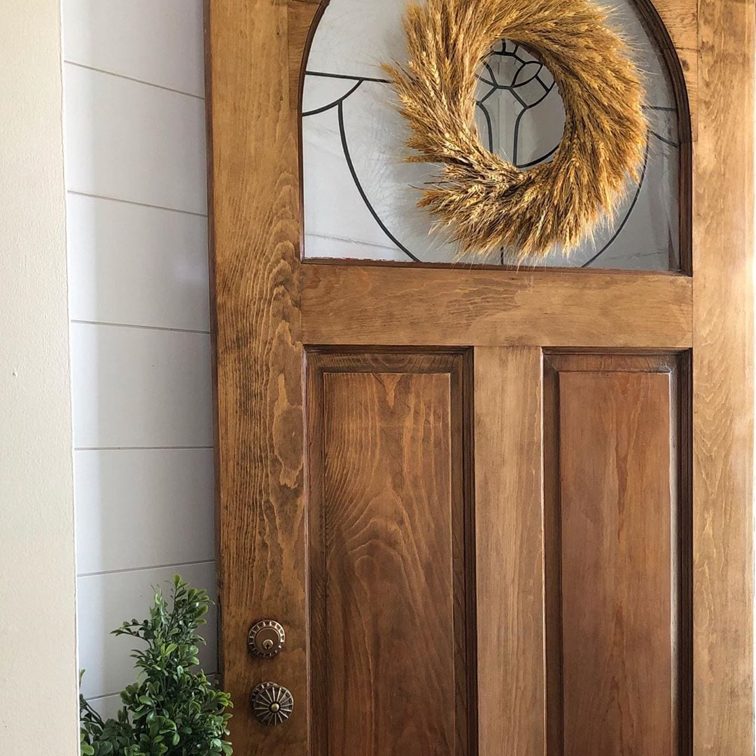 wooden front door with fall themed wreathe