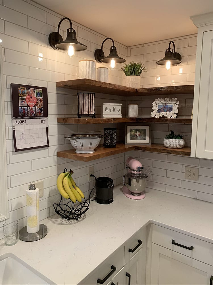 3 floating shelves in the corner of a kitchen