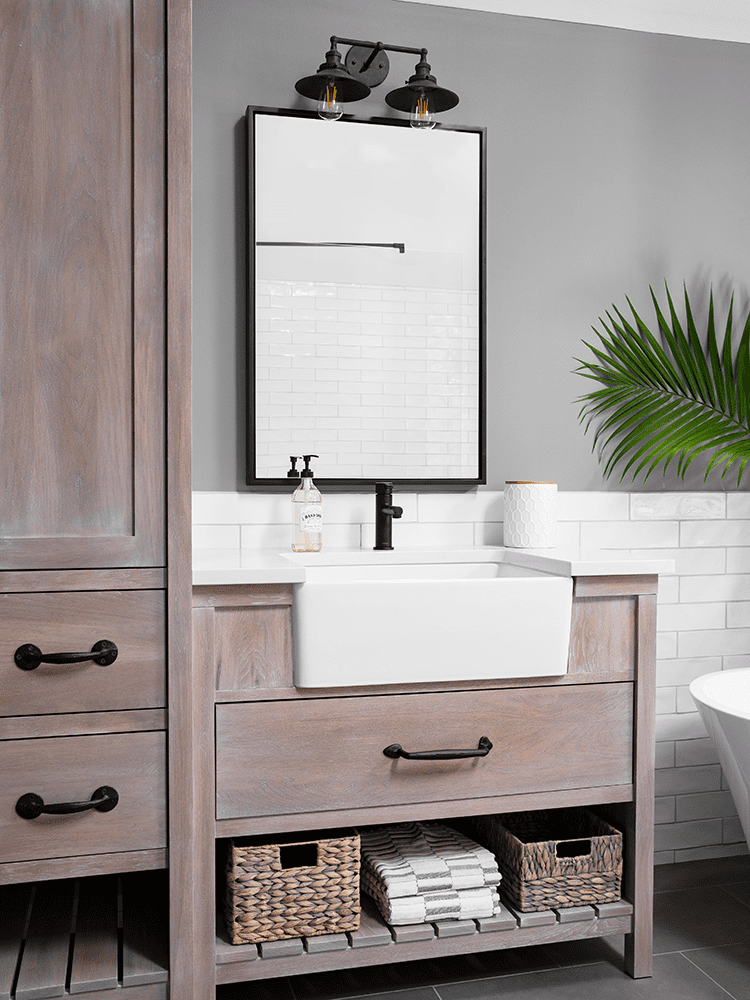 closeup of light brown amish cabinets with farmhouse sinks in bathroom