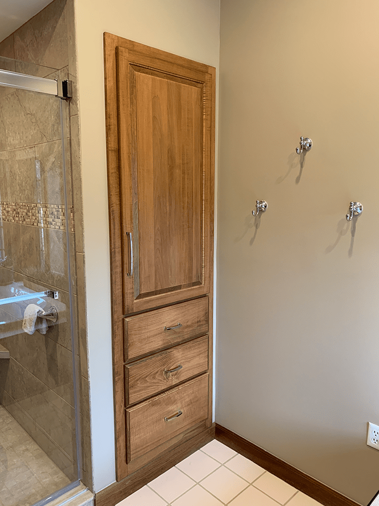 tan bathroom with 3 hooks on wall and brown stained bathroom cabinetry
