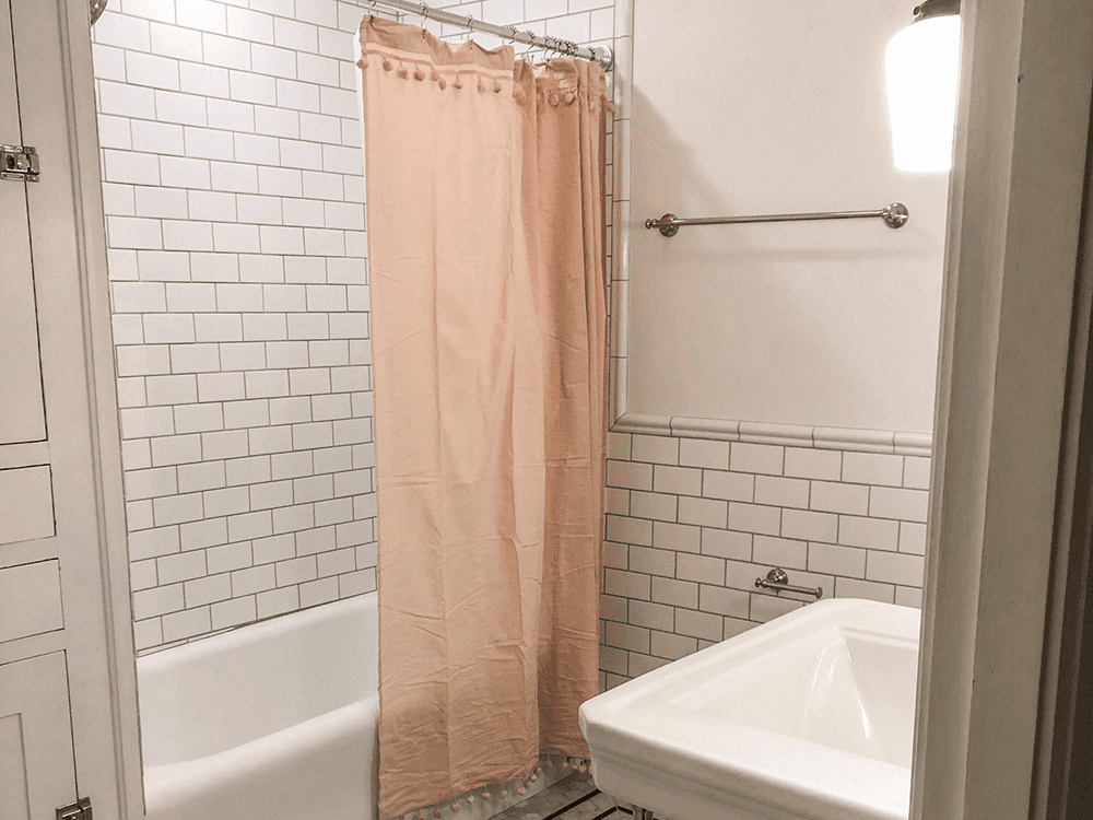 small white bathroom with light pink shower curtain