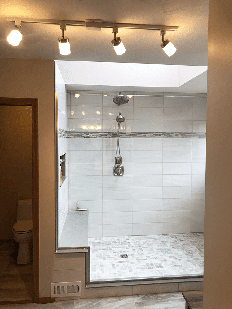 wide shower with glass wall and bench area in shower