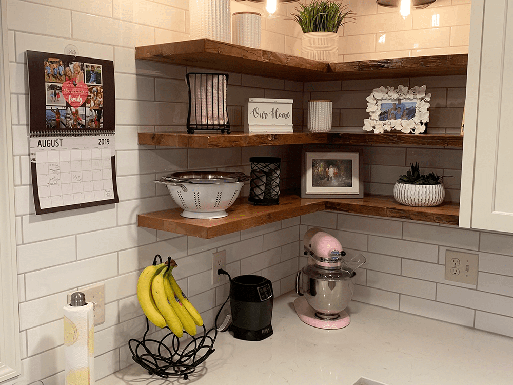 3 floating wood shelves in corner of kitchen with decor