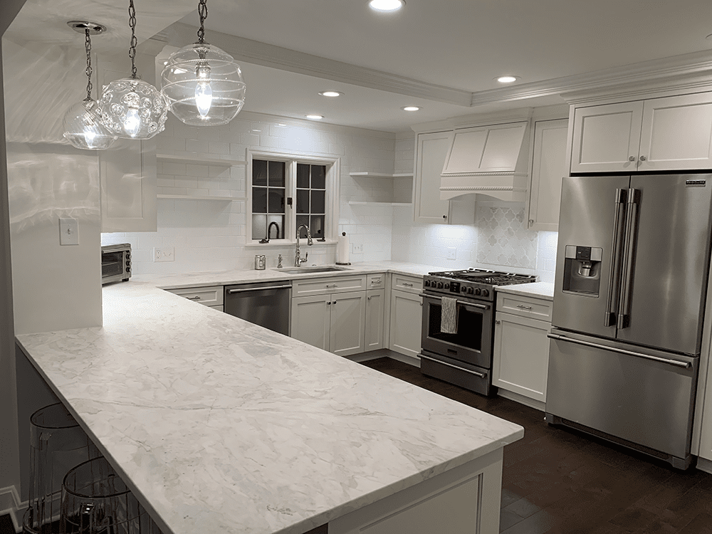 kitchen with off white cabinets and floating shelves on one wall with 3 hanging lights