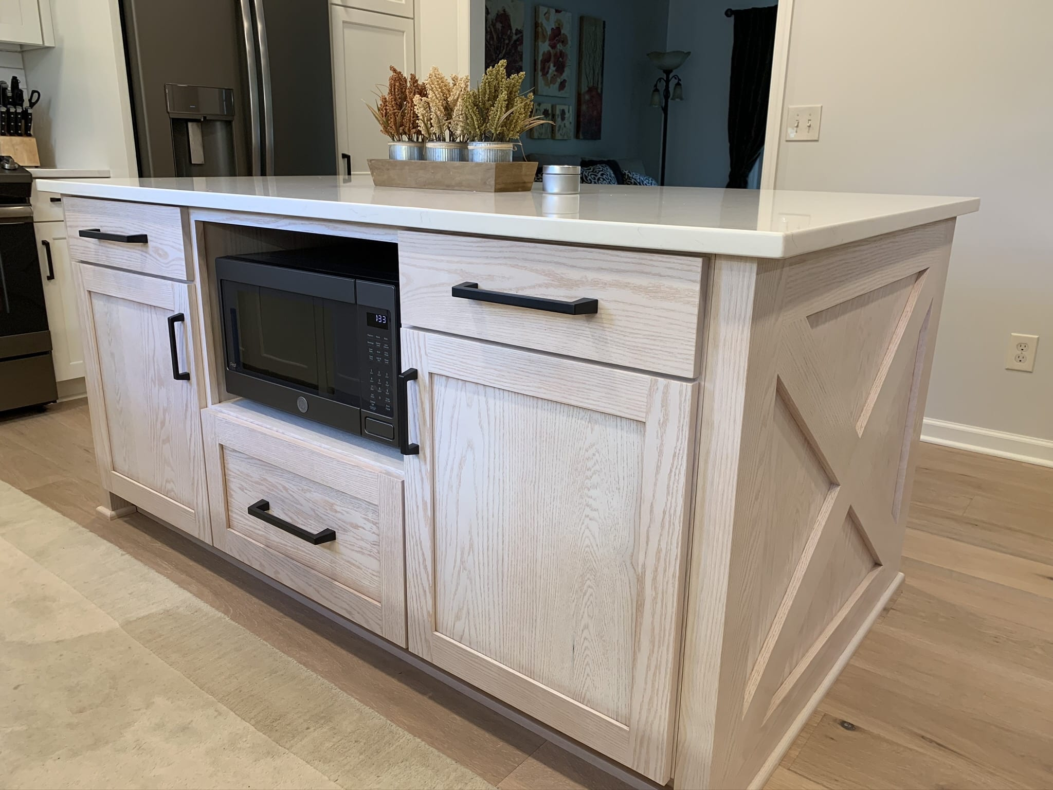 rustic kitchen island with unpainted cabinets and fall plant decor on top