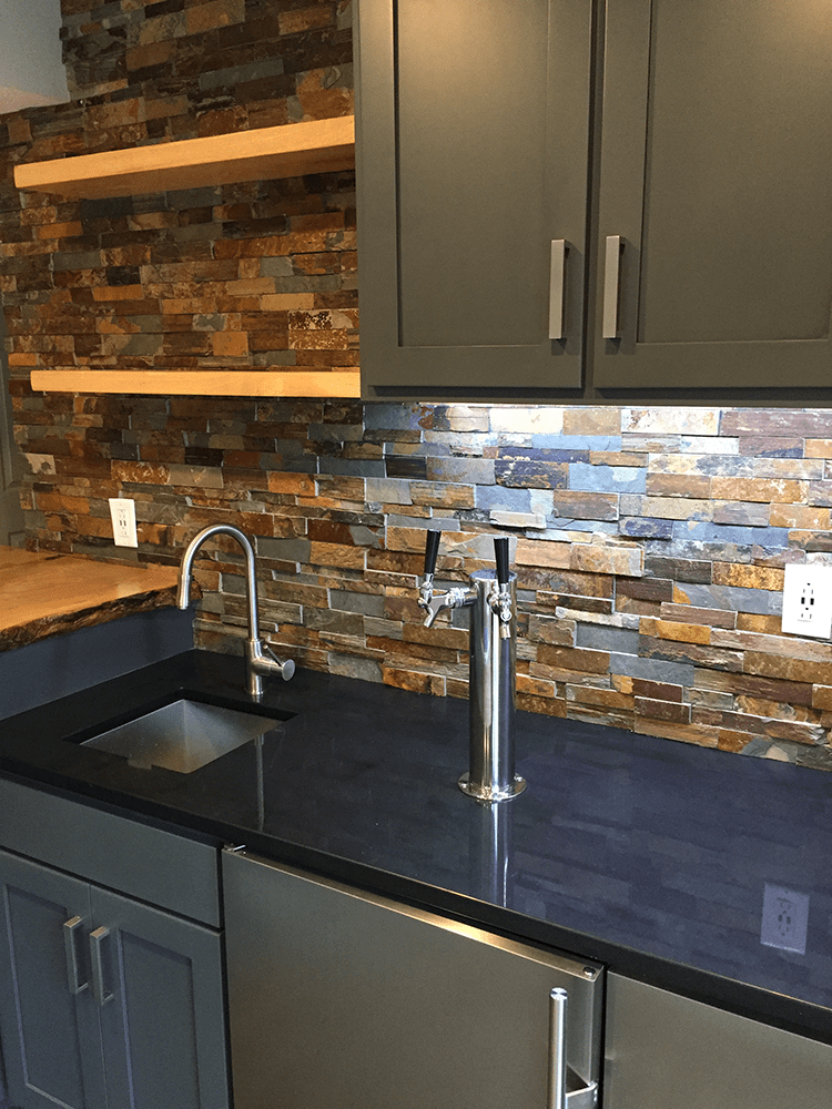 kitchen with dark blue and gray cabinets and stone backsplash