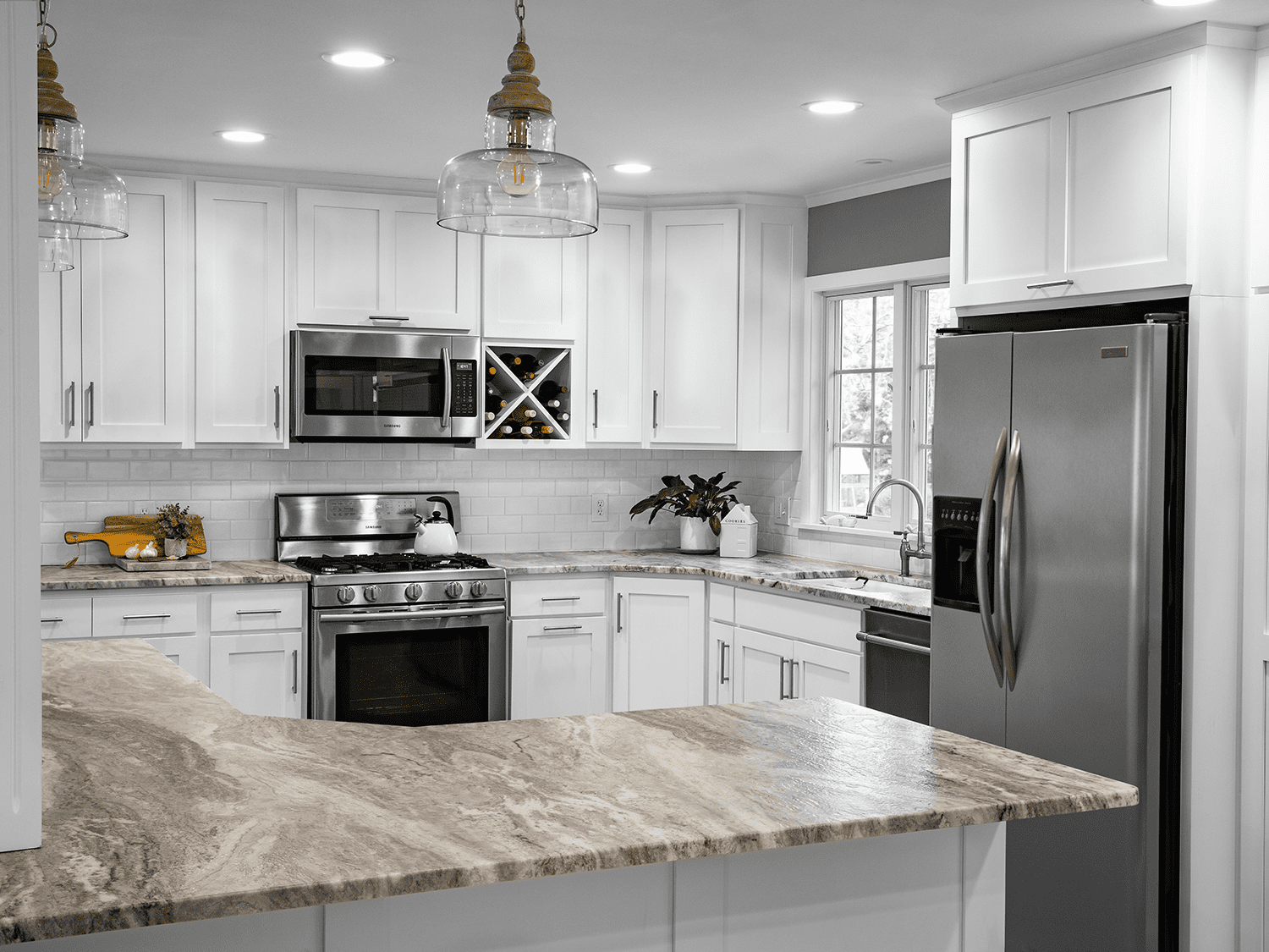 bright white kitchen with marble countertops and brown bar stools