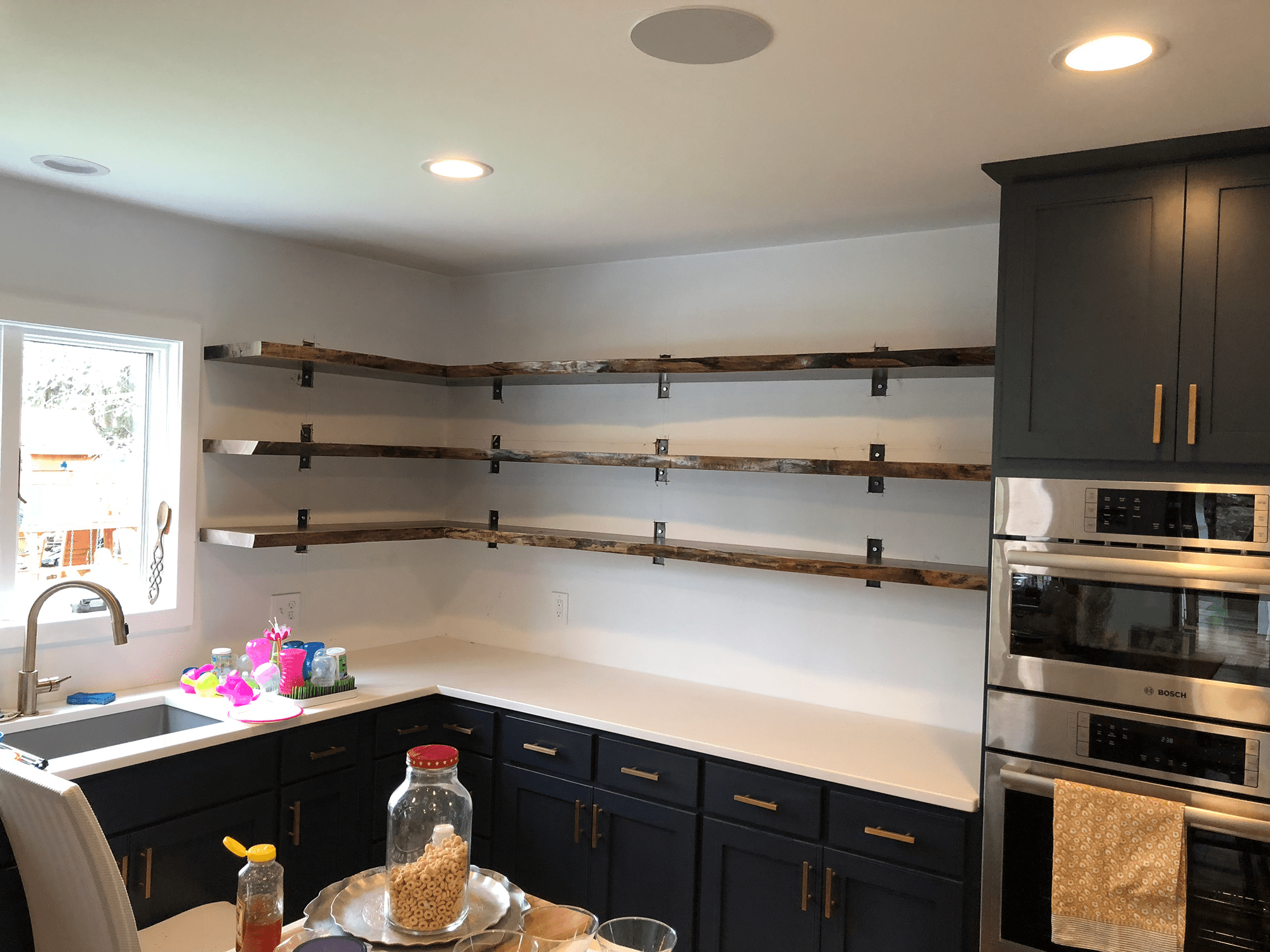 kitchen with 3 floating shelves and dark blue cabinets