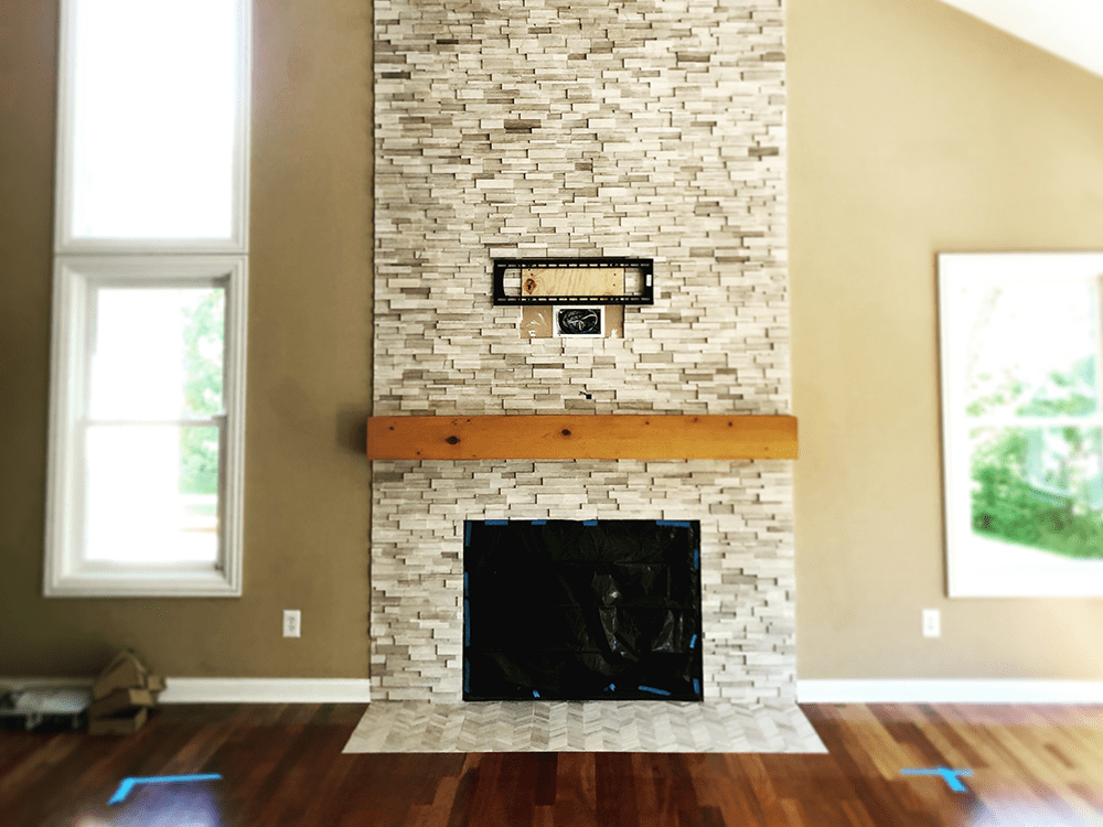 fireplace with stone mantle that goes to ceiling