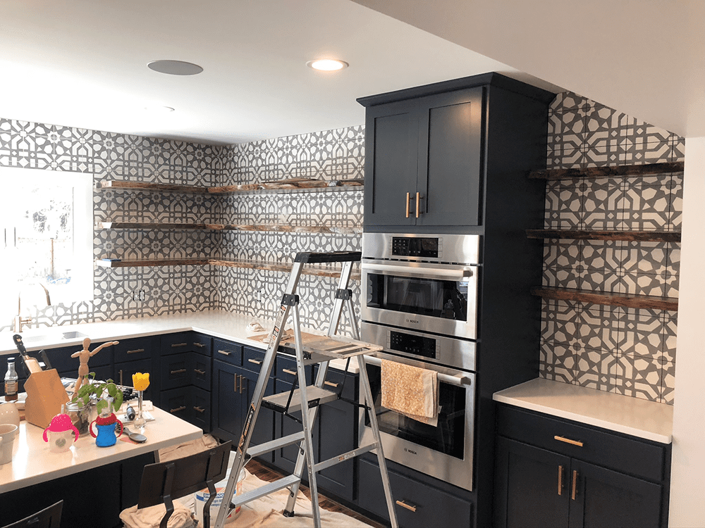 progress pic of kitchen with accented walls dark blue cabinetry and 3 floating shelves all around