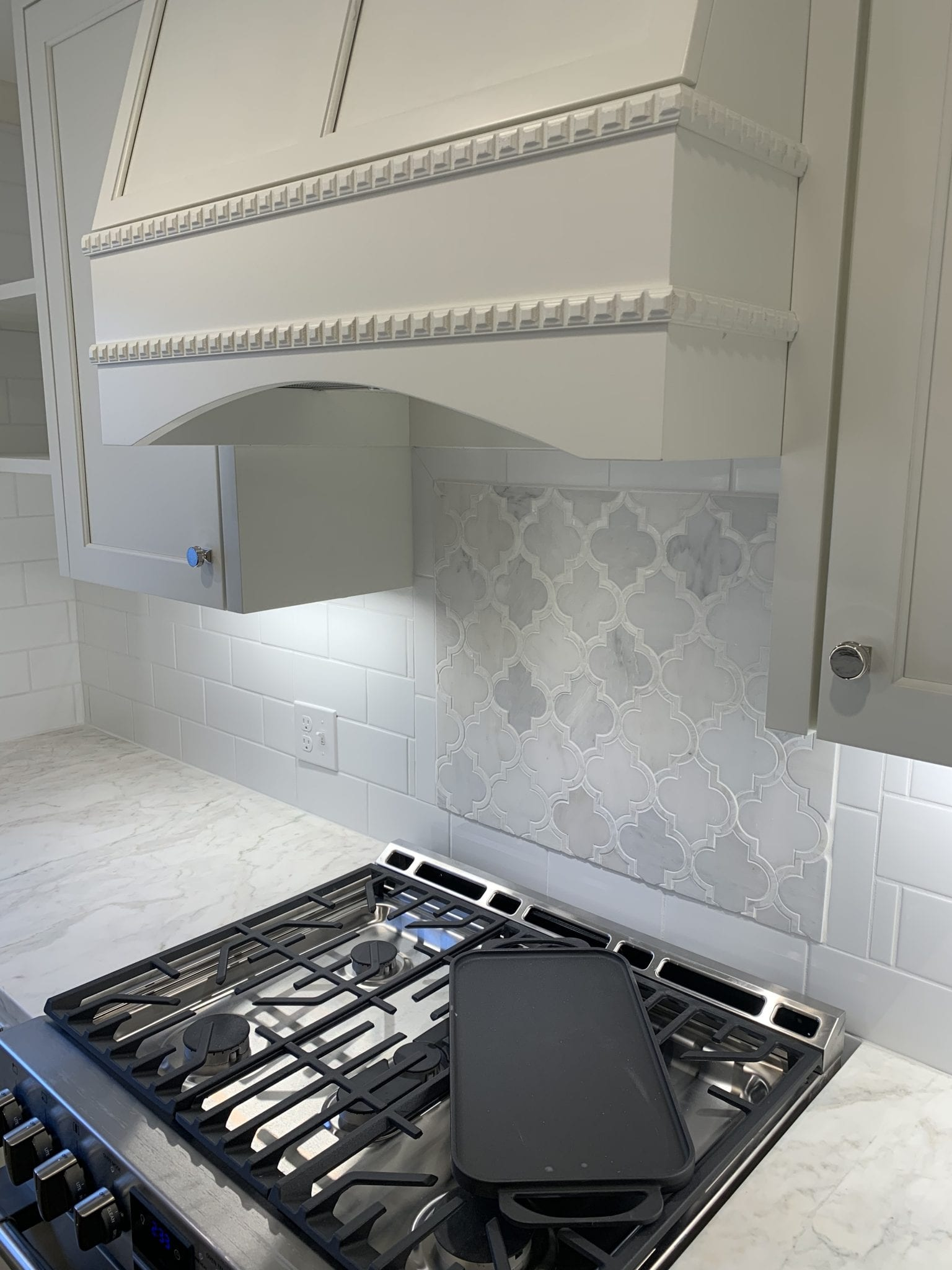 close up of stove with white accented backsplash